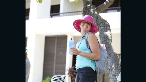 """Fit Nation athletic director April Burkey rocks a pink hat while waiting for the """"Lucky 7"""" to get fitted for rental bikes in Hawaii."""