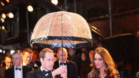 """Prince William kept his wife dry at the London premiere of """"War Horse"""" on January 8, 2012. She wore a black lace <a href=""""http://nymag.com/daily/fashion/2012/01/kate-middleton-war-horse-premiere-temperley.html"""" target=""""_blank"""" target=""""_blank"""">Alice by Temperley</a> gown and carried a black clutch."""