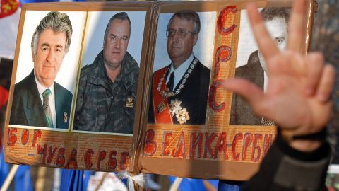 """Serb nationalists protest against the U.S. and the U.N. war crimes court in Belgrade in December 2006. Their posters show pictures of Karadzic, Mladic and Vojislav Seselj with the Cyrillic writing meaning: """"God saves the Serbs"""" and """"Great Serbia."""""""