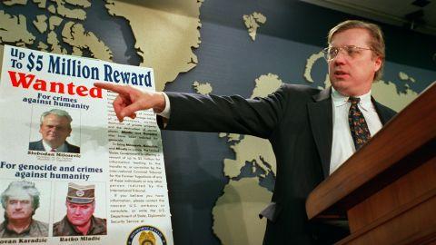 David Scheffer, U.S. Ambassador at large for war crimes points to a wanted poster showing Yugoslav President Slobodan Milosevic,  Karadzic and Mladic in March 2000.