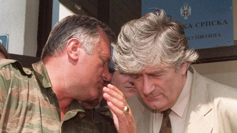 Bosnian Serb leader Radovan Karadzic, right, confers with his military chief during a meeting with the press in Pale on August 5, 1993.
