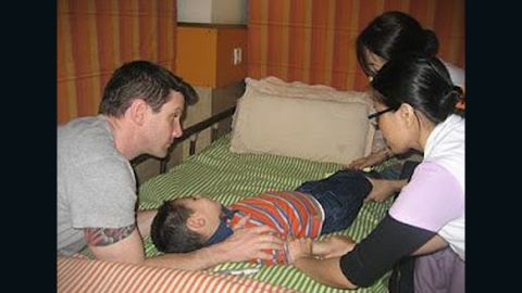 Cash is comforted by his father, Josh Burnaman, while nurses treat the boy during therapy at NuTech Mediworld in 2010.