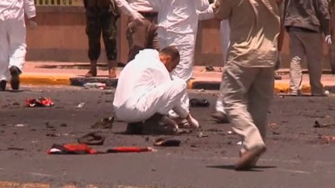 A forensic team member examines debris after a suicide bomber blow himself up at a military parade rehearsal in Sanaa, Yemen.