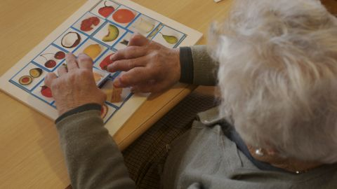 A woman with Alzheimer's at a care center works a puzzle to exercise her mind.