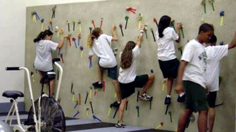 Students at a middle school in Miami climb on a traversing wall in a Fit-Tech Wellness Lab.