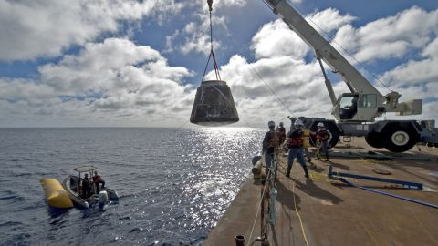 The first Dragon capsule to make it into orbit and return to Earth was launched in December 2010. Here, crews haul the charred capsule out of the ocean.