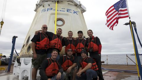 Dragon's recovery team poses in front of the first commercial capsule to reach orbit and return safely to Earth.