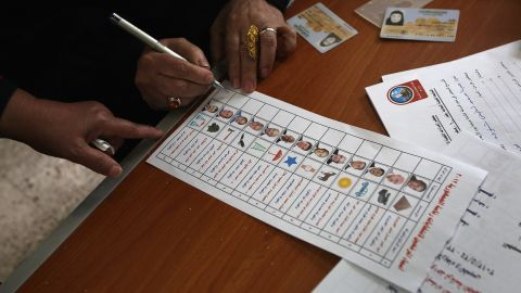 A voter studies her ballot Wednesday in Cairo. Thirteen candidates are competing in the wide-open race, but two withdrew after ballots were printed.