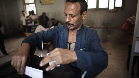 An Egyptian man casts his ballot at a Cairo polling station. Some Egyptians told CNN that they waited up to four hours Wednesday to vote.