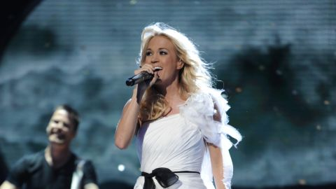 """Carrie Underwood went from college student to winner of season 4 in 2005. Her debut album, """"Some Hearts,"""" was certified seven times platinum, and she has gone on to win multiple Grammy Awards. In 2013, she starred in a live television version of """"The Sound of Music."""" Married to hockey player Mike Fisher, Underwood gave birth to their first child, son Isaiah Michael Fisher, in February 2015."""