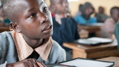 A young Masai boy listens to his teacher as he follows the lesson in a Kenyan textbook on his e-reader.