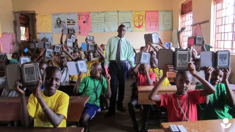 Students and their teacher at Humble School in Mukono, Uganda. E-readers are considered an effective approach to encouraging literacy in parts of the developing world where traditional books are scarce, because they give students direct access to a greater number of titles.