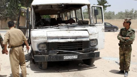 Syrian military officers inspect a damaged bus following a deadly explosion Wednesday.