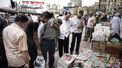 Egyptians read the front page of newspapers for sale outside of Al-Fatah Mosque in Cairo on Friday, May 25.