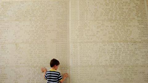 A boy traces the names of soldiers who died during World War II at a service Sunday to mark Memorial Day at the Manila American Cemetery in the Philippines.