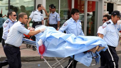 A survivor receives medical care outside of the Villaggio mall. More than a dozen people were injured.