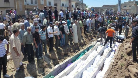 A handout picture released by the Syrian opposition's Shaam News Network shows people at a mass burial on Monday.