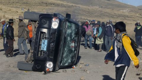 Locals surround a damaged car during a protest against Swiss-owned mining company Xstrata.