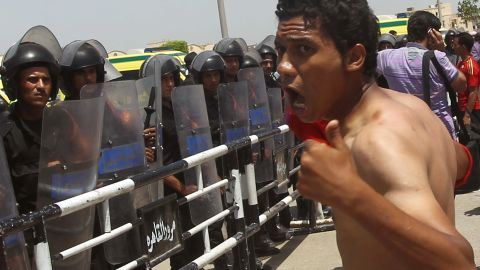 An anti-Mubarak protester shouts before a line of riot police guarding the Cairo courthouse.