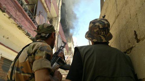 Armed militiamen look at smoke billowing in Tripoli's Sunni Muslim neighborhood of Bab al-Tabbaneh on Saturday.