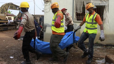 Rescue workers remove a victim of Sunday's plane crash in a Lagos, Nigeria, residential area on Monday, June 4. All 153 people aboard were killed.