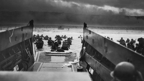 The Allied Forces stromed the beaches of Normandy, france on June 6, 1944.  Here American troops hit the water from one of the landing craft.  Soldiers on shore are lying flat under German machine gun fire. Robert F. Sargent, a Coast Guard photographer, took this view from a landing barge.