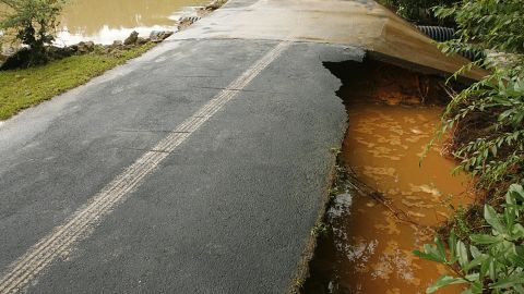 In west Mobile, Alabama, heavy rain washed out an earthen dam in a subdivision Saturday, flooding Mitch Smith's property and damaging his driveway.
