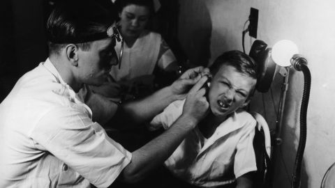 A young patient gets his ears examined in 1935.