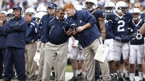 Penn State head football coach Joe Paterno talks with assistant coach Mike McQueary during the 2010 Capital One Bowl in Orlando.