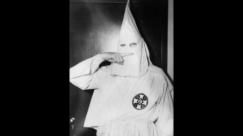 Stetson Kennedy, an activist who infiltrated the Ku Klux Klan and wrote about it in his book Southern Exposure, poses in KKK garb in 1947 and demonstrates the sign for the Oath of Secrecy.