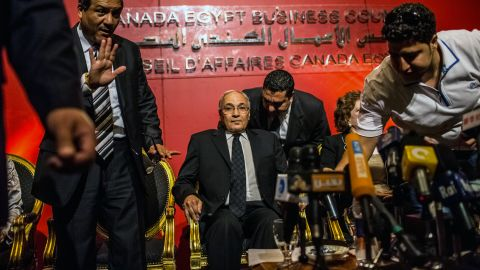 Former Prime Minister Ahmed Shafiq, center, is seated before addressing a business conference in Cairo on Wednesday.