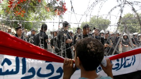 A boy peers through barbed wire at Egyptian military police standing guard outside the Constitutional Court in Cairo on Thursday, June 14.