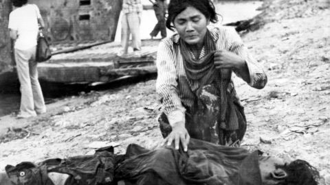 A woman cries next to a dead body, 17 April 1975 in Phnom Penh, after the Khmer Rouge enter the Cambodian capital and establish government of Democratic Kampuchea (DK). (Photo credit should read CLAUDE JUVENAL/AFP/Getty Images)