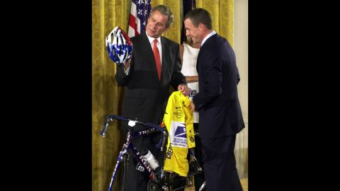 After winning the 2001 Tour de France, Armstrong presents President George W. Bush with a U.S. Postal Service yellow jersey and a replica of the bike he used to win the race.