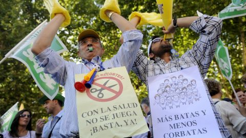 Health workers in Seville protest against government austerity measures on June 12, 2012. The campaigners display banners saying 'Don't play with health' and 'More gowns and fewer ties.'