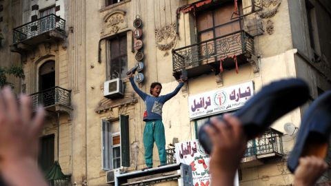 An Egyptian boy waves his shoes as he joins supporters of the Muslim Brotherhood in a protest in Cairo's Tahrir Square against Mubarak-era prime minister and presidential candidate Ahmed Shafik after Egypt's top court rejected on Thursday a law barring him from standing in a tense presidential poll runoff.