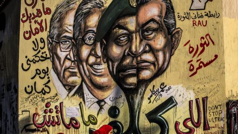 People walk past graffiti showing faces of ousted Egyptian president Hosni Mubarak, right; Field Marshal Hussein Tantawi, second right; former Secretary General of the Arab League Amr Mussa, second left, and former prime minister and presidential candidate Ahmed Shafiq, left, at Tahrir square.