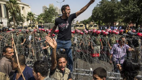 A protester stands on a barricade of barbed wire as Egyptian military police stand guard. Egypt's Supreme Constitutional Court ruled that the Islamist-led parliament must be immediately dissolved.