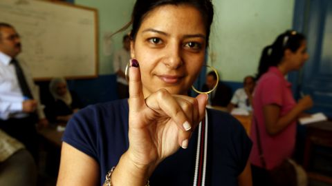 An Egyptian woman holds up an ink-stained finger after casting her vote at a polling station in Cairo.