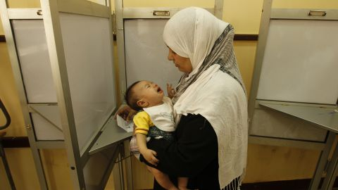 An Egyptian woman holds her baby as she prepares to vote at a polling station in Cairo.