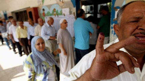 An Egyptian man shows off his little finger covered in indelible ink after casting his vote at a polling station in Cairo.