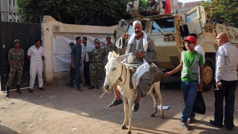 An Egyptian man on his donkey shows his ink-stained finger after casting his ballot.