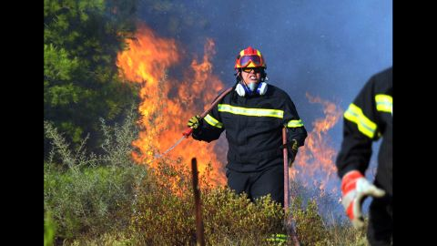A firefighter works on extinguishing a brush fire in the eastern Athens area of Keratea. Two brush fires broke out in Greece on Saturday, including one near seaside resorts close to Athens, just a day ahead of crucial elections.