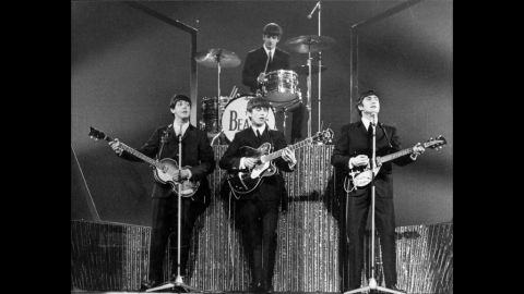 """The Beatles, whose arrival in the U.S. in 1964 set off """"Beatlemania,"""" perform on stage at the London Palladium in 1963."""