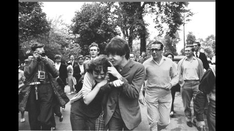 """McCartney is hugged by an adoring fan after arriving at rehearsal for the TV show """"Jukebox Jury"""" in London in 1964."""