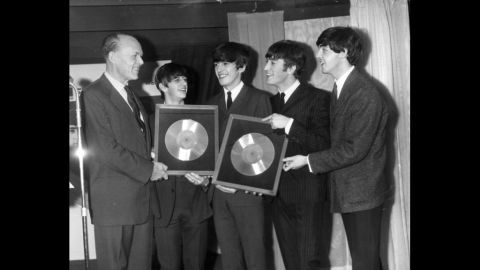 """Sir Joseph Lockwood, chairman of EMI Music, presents The Beatles with two silver records for their albums """"Please, Please Me"""" and """"With The Beatles,"""" which reached 250,000 sales."""