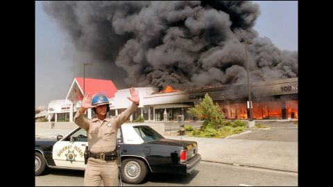 A California Highway Patrol officer directs traffic around a shopping center engulfed in flames on April 30.