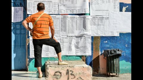 A man ponders the electoral board at a polling station in Athens before voting Sunday.