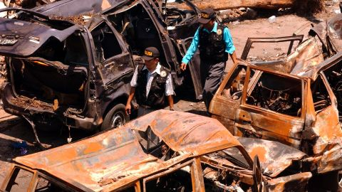 """Indonesian police investigators walk through the wreckage of cars left twisted and burnt after the bomb attack in Bali. One witness, Nicolle Haigh, told police: """"I've been told that there was about 45 seconds between explosions, but it felt like 10 seconds. One moment I was talking to friends, and the next was like being in a war zone."""""""