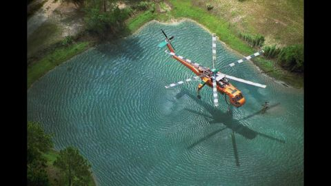 """This is Greer's award-winning image of an Erickson Air-Crane dipping into a pond to fill its tank on the Oakhead Complex Fire in Osceola National Forest, Florida. The image won first place in the """"aerial resources"""" category of a Fire & Aviation Management photo contest in 2004."""